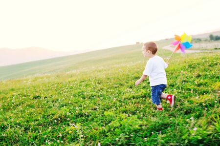 little happy child play with windmil toy and have ve fun while running on beautiful meadow at sunset photo
