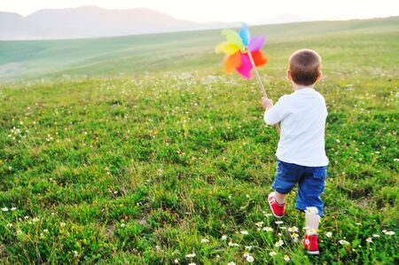 ve: little happy child play with windmil toy and have ve fun while running on beautiful meadow at sunset Stock Photo