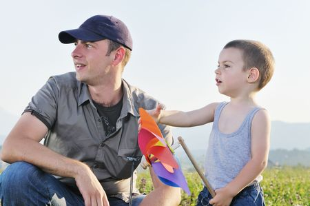 little happy child and young father play with windmil toy and have fun while running on beautiful meadow at sunset