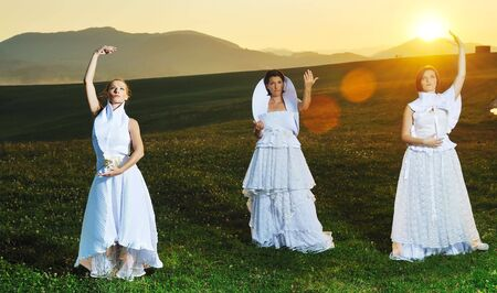 group of bride run on meadow at sunset after wedding party photo