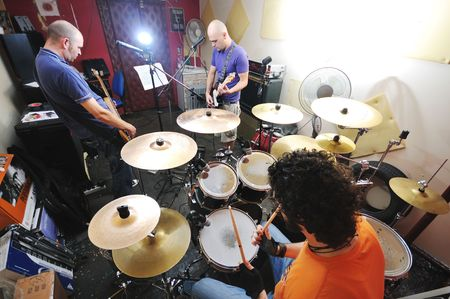 string together: young music player and band friends have training in home garage