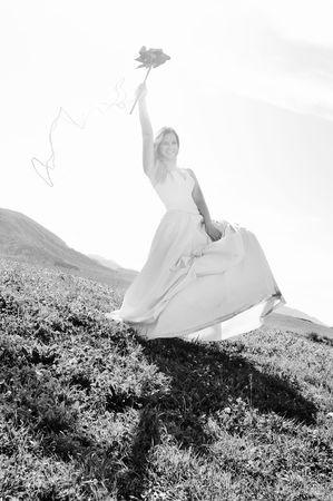 Feliz novia hermosa joven después de la ceremonia de la boda evento divertirse al aire libre en la pradera al atardecer con molino de viento de juguete y que representa la energía inteligente Foto de archivo - 5463228