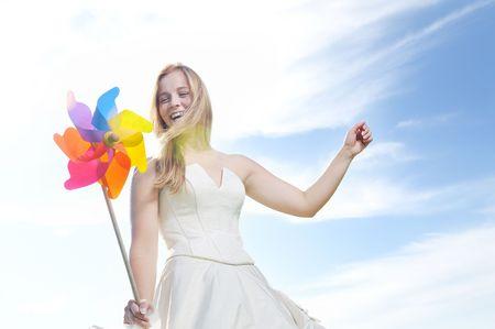 molino: feliz novia hermosa joven después de la ceremonia de la boda evento divertirse al aire libre en la pradera al atardecer con molino de viento de juguete y que representa la energía inteligente Foto de archivo