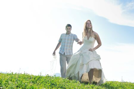 happy bride and groom walking and run on beautiful meadow outdoor at sunset  photo