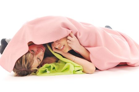 happynes: two youg happy giril woman smiling unger blanket isolated representing concept of lesbian love, happynes and softnes Stock Photo