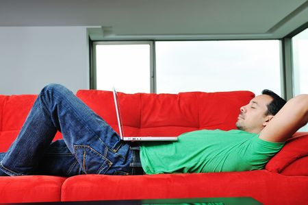 young man relax on red sofa and work on laptop at home indoor Stock Photo - 5551824