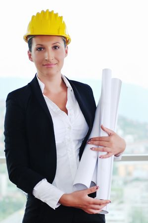 female architect: young architect woman in business suit portrait with yellow hemet and blueprints