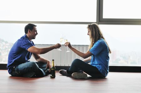 happy couple at big bright comfort apartment celebrate with glasses of champagne photo