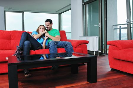 happy couple relaxing on red sofa in big bright new apartment photo