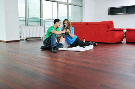 frau sitzt am boden: gl�ckliche Paar bei gro�en hellen Komfort-Appartement feiern Sie mit Gl�ser Champagner