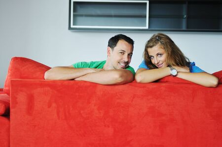 happy couple relaxing on red sofa in big bright new apartment Stock Photo - 5557222