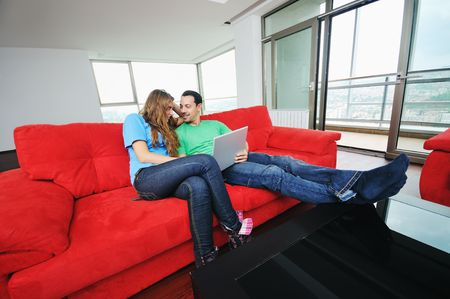 happy young couple have fun and relax at comfort bright appartment and work on laptop computer Stock Photo - 5637150