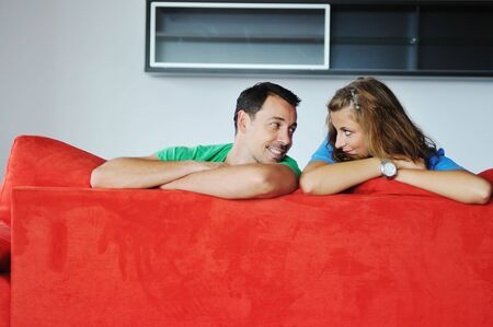 happy couple relaxing on red sofa in big bright new apartment Stock Photo - 5557223