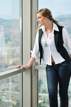 young woman looking and waiting on window photo