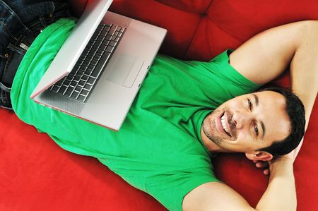 young man relax on red sofa and work on laptop at home indoor  Stock Photo