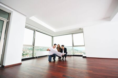 agente comercial: joven pareja que la compra de viviendas nuevas con el agente de bienes ra�ces y grandes planes de futuro luminoso apartamento confort y teniendo clave