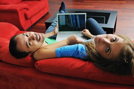 happy young couple have fun and relax at comfort bright apartment and work on laptop computerhappy young couple have fun and relax at comfort bright appartment and work on laptop computer photo