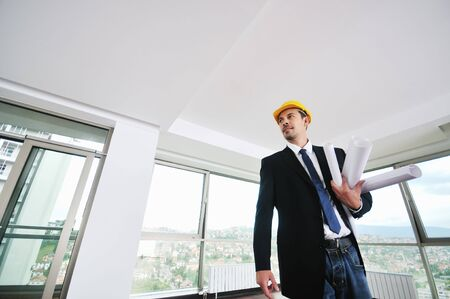 happy young architect portrait with helmet and blueprints indoor at new big bright appartment and construction site photo