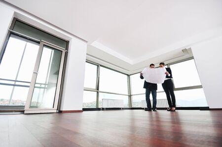 jonge arhitect groep in grote heldere moderne nieuwe appartement op zoek blauwdrukken en bouw plannen