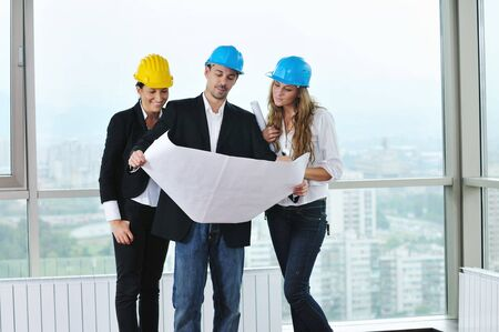 arhitect: young arhitect group in big bright modern new apartment looking blueprints and building plans
