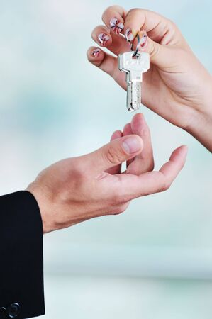 man and woman hand closeup with home keys representing buying and selling new apartment and real estate concept  Stock Photo
