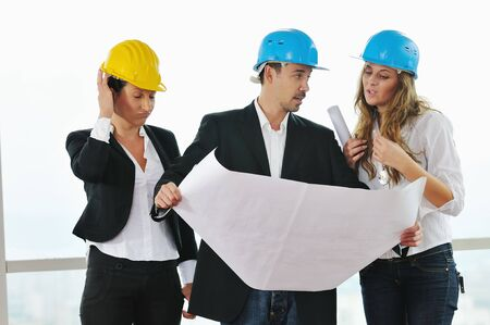young arhitect group in big bright modern new apartment looking blueprints and building plans Stock Photo - 5552856
