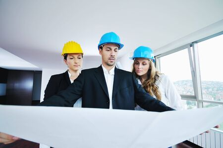 young arhitect group in big bright modern new apartment looking blueprints and building plans Stock Photo - 5552858