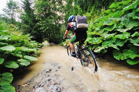 young man drive mountain bike over water river photo