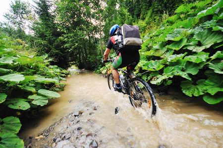 dirt road recreation: young man drive mountain bike over water river