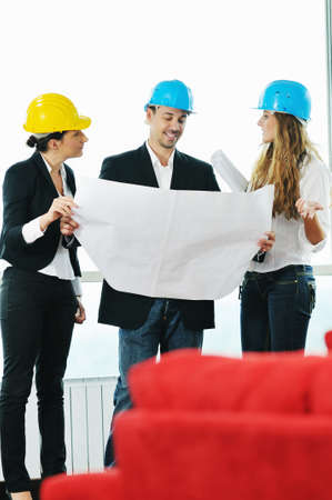 young arhitect group in big bright modern new apartment looking blueprints and building plans Stock Photo - 5686351