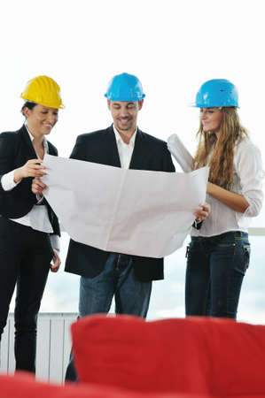 young arhitect group in big bright modern new apartment looking blueprints and building plans photo