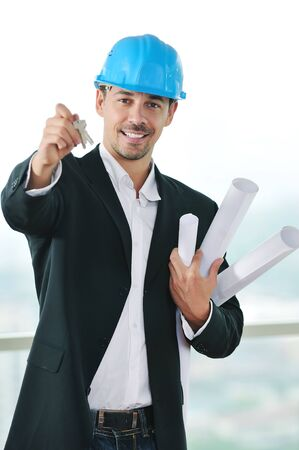 young business man isolated on white holding new home keys and representing sucess in real estate industry photo
