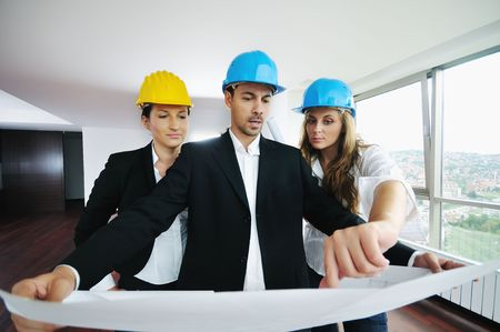 young arhitect group in big bright modern new apartment looking blueprints and building plans Stock Photo - 5686717