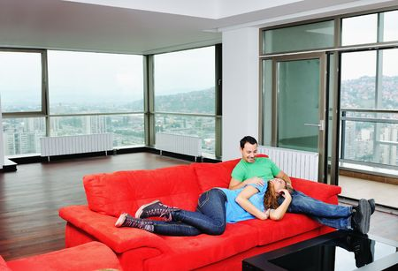 condominium: happy couple relaxing on red sofa in big bright new apartment