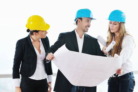 young arhitect group in big bright modern new apartment looking blueprints and building plans Stock Photo - 5686481