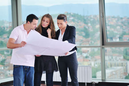 happy young couple buying new home with real estate agent and  looking big comfort bright apartment plans and taking key Stock Photo