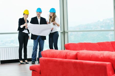 young arhitect group in big bright modern new apartment looking blueprints and building plans Stock Photo - 6226861