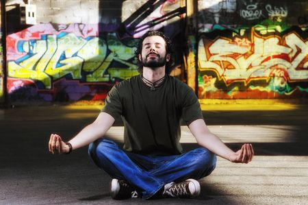 enviroment: young happy man in urban enviroment practicing and meditating yoga in lotus position  Stock Photo