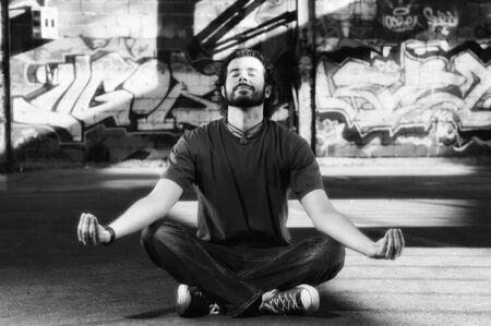 young happy man in urban enviroment practicing and meditating yoga in lotus position  photo