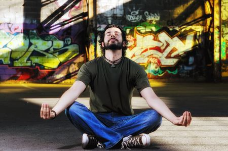man meditating: young happy man in urban enviroment practicing and meditating yoga in lotus position  Stock Photo