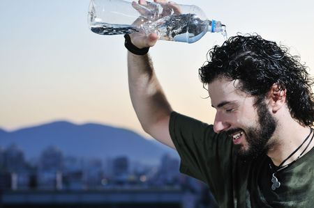 young man dring fresh water from bottle outdoor photo