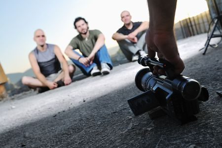 three young man siting on ground while modern video camera recording photo
