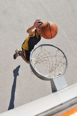gorup of young boys who playing basketball outdoor on street with long shadows and bird view perspective photo