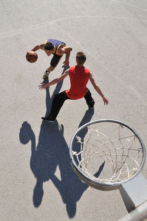 bird view: gorup of young boys who playing basketball outdoor on street with long shadows and bird view perspective