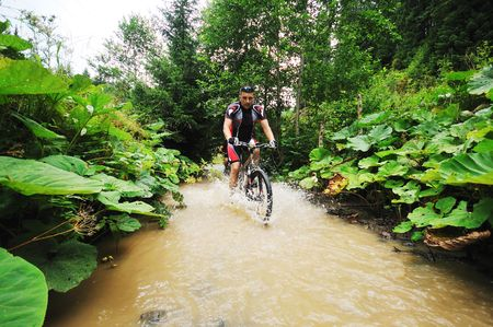 young man drive mountain bike over water river photo