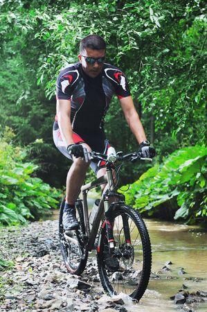 urban jungle: healthy lifestyle and fitness concept with mount bike man who ride bike  outdoor