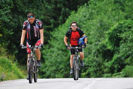 two friends have fun outdoor in nature and ride  on muntain bike photo