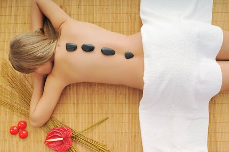 volcanic stones: young healthy woman in wellness and spa studio have Massage with hot volcanic stones