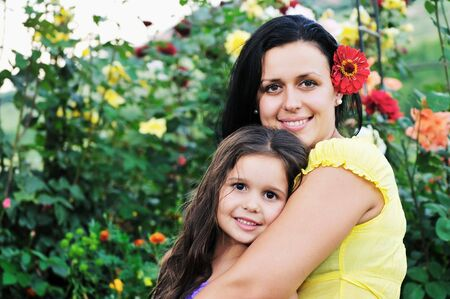 beautiful mom and daughter outdoor in garden  together with flower have fun and hug Stock Photo - 5857505