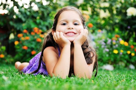happy young girl children relax lie and have fun on grass with flower Stock Photo
